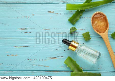 Aloe Vera Gel On Wooden Spoon With Aloe Vera And Oil Bottle On Blue Wooden Table. Top View.