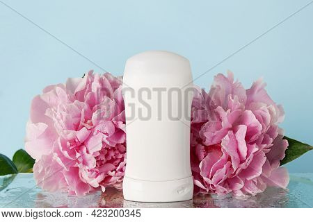 Deodorant With Pink Flowers On Blue Background With Water Drops