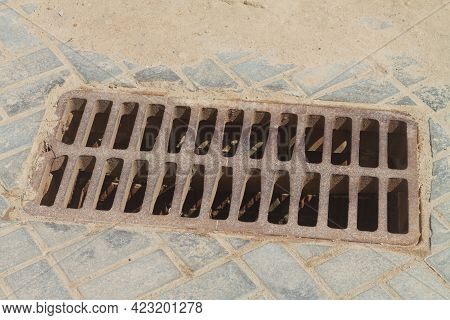 Metal Storm Drain With Holes For Water Drainage In The Road Paved With Paving Slabs In The City.