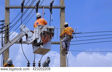 Group Of Electrician With Crane Truck Are Working To Maintenance Electrical Transmission On Power Po