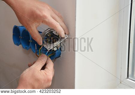 An Outlet Receptacle, Electrical Socket, Power Plug Installation. An Electrician Is Installing, Conn