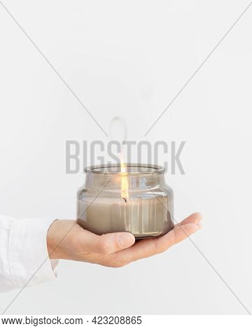 Woman Hand Holds Lit Scented Candle In Gray Glass Jar With Natural Ingredients On White Background.