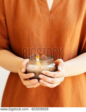 Woman Hand Holds Lit Scented Candle In Glass Jar With Natural Ingredients On Terracotta Linen Backgr