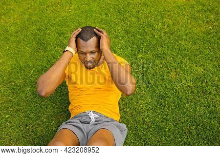 Young Sporty Focused Afro American Male Lying On Green Grass Doing Morning Workout Outdoors, Healthy