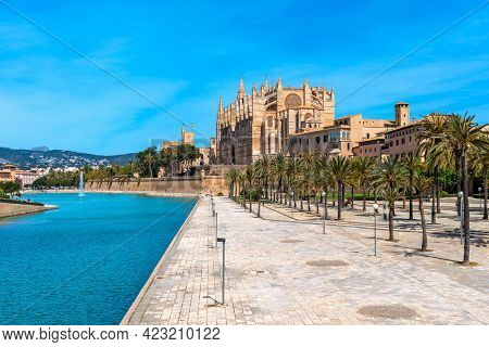 Artificial pond in Parc de La Mar and famous La Sue Cathedral under blue sky in Palma de Mallorca, Spain.