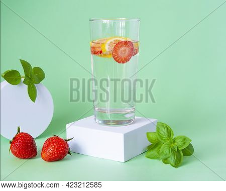 Refreshing Summer Drink With Strawberries, Lemon And Basil In A Glass On A Green Background. The Gla