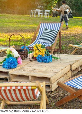 Beautiful Artificial Bouquets Of Various Colors Placed On Wooden Table Among Deck Chairs In Garden.