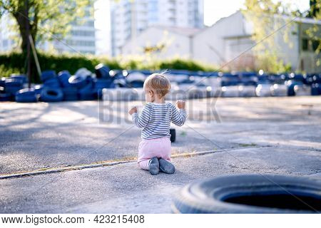 Child Is Kneeling Against The Background Of Car Tires In The Parking Lot. Back View