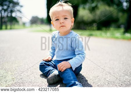 Little Girl With A Ponytail Sits On The Road In The Park