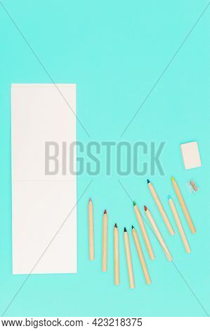Flat Lay With Colored Pencils And Open Sketch Pad For School, Education. Set Of Wooden Colorful Penc
