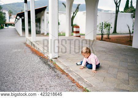 Little Girl Sits On A Tile In A Long Pavilion In The Park