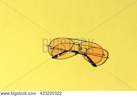 Yellow Sunglasses Isolated On A Bright Background. Hard Shadows From The Sun At Noon. Leisure, Trave
