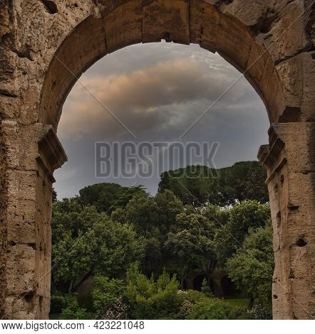 Italian Landscape Through An Archway Of The Colosseum In Rome, Italy.