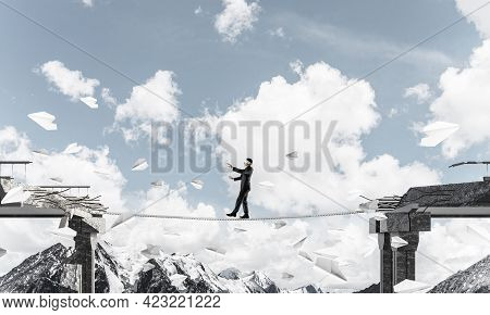 Businessman Walking Blindfolded On Rope Among Flying Paper Planes And Above Huge Gap In Bridge As Sy