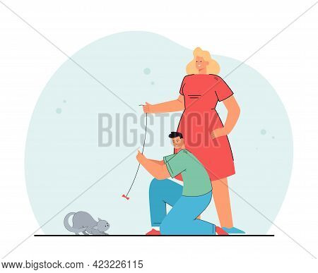 Man And Woman Playing With Cat. Happy Couple Spending Time Together, Teasing Kitten With Bow On Stri