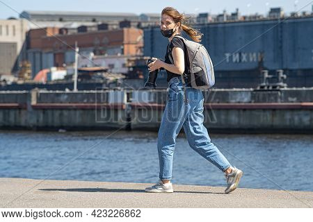 The Photographer Girl On The Pier Holds A Camera In Her Hand. As She Ran Past, She Smiled At Her Col