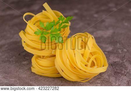Fresh Italian Tagliatelle Pasta On A Gray Background. Close-up.
