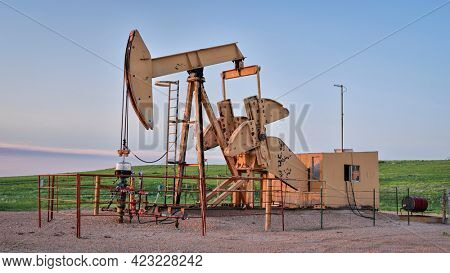 oil extraction facility with a pumpjack in a green prairie, Pawnee National Grassland in Colorado in late spring.