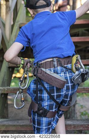 Forest Adventure Park. A Child With Special Equipment Overcomes Obstacles In The Forest Adventure Pa