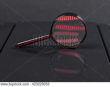 Magnifying Glass Or Zooming Lens On Dark Black Background With Red Light Flares. Searching And Detec