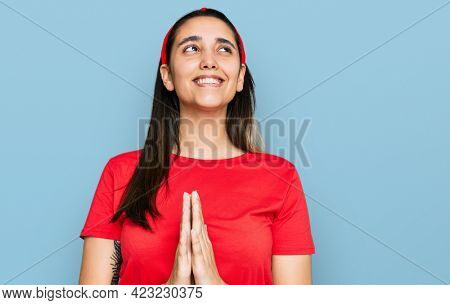 Young hispanic woman wearing casual clothes begging and praying with hands together with hope expression on face very emotional and worried. begging.