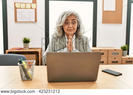 Middle age businesswoman sitting on desk working using laptop at office praying with hands together asking for forgiveness smiling confident.