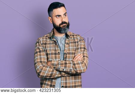 Hispanic man with beard with arms crossed gesture smiling looking to the side and staring away thinking.