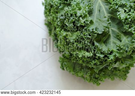 Kale On A Cutting Board, On The Table Top. Superfood On Light Background