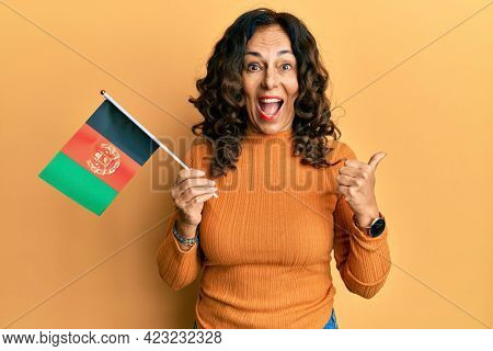 Middle age hispanic woman holding afghanistan flag pointing thumb up to the side smiling happy with open mouth