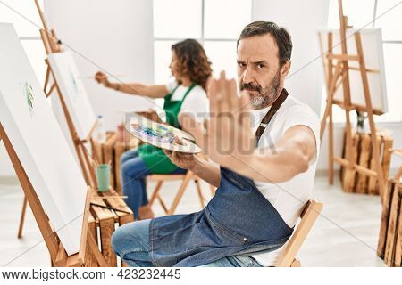 Hispanic middle age man and mature woman at art studio with open hand doing stop sign with serious and confident expression, defense gesture