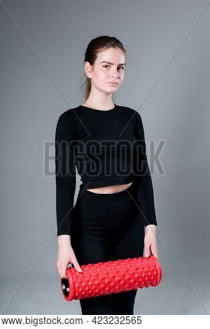 Beautiful Girl Trainer In A Black Top And Leggings Holds Fascia In Her Hands While Standing On A Gra