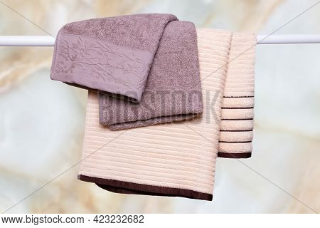Hanging Towels. Closeup Of Violet And Beige Soft Terry Bath Towels Hang On A Clothes Rail In Front O