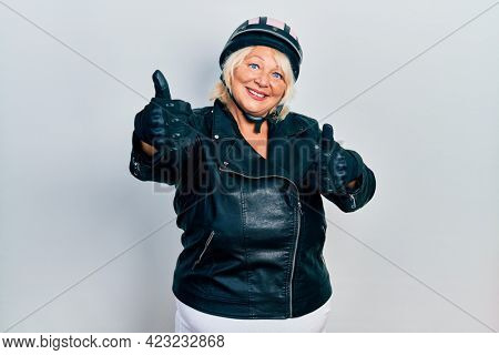 Middle age blonde woman holding motorcycle helmet approving doing positive gesture with hand, thumbs up smiling and happy for success. winner gesture.
