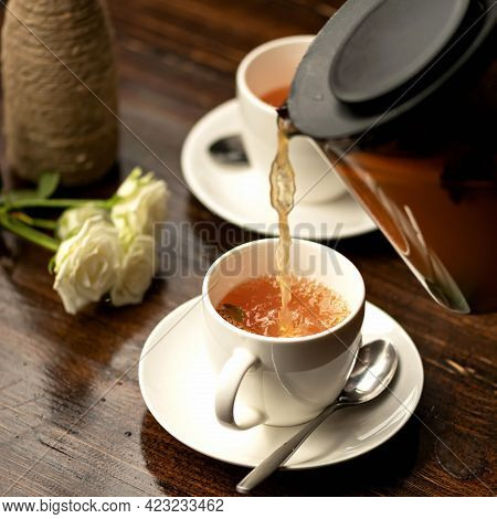 Black Tea Pouring From Clear Teapot In Teacup And Bouquet Of Roses Flowers On Wooden Table. Romantic
