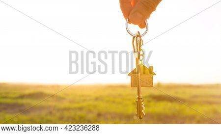 House Key With Keychain In Hand. Background Of Sky, Sunlight And Field. Dream Of Home, Building A Co