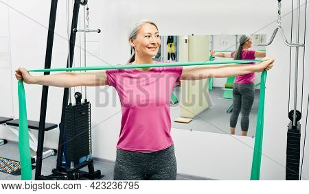 Patient Woman Doing Exercises For Recovery Arms After Injury Using Stretching Resistance Band At A R