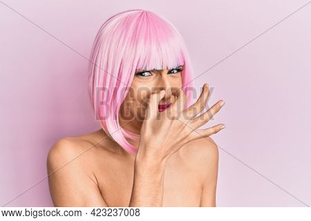 Young man wearing woman make up wearing pink wig smelling something stinky and disgusting, intolerable smell, holding breath with fingers on nose. bad smell
