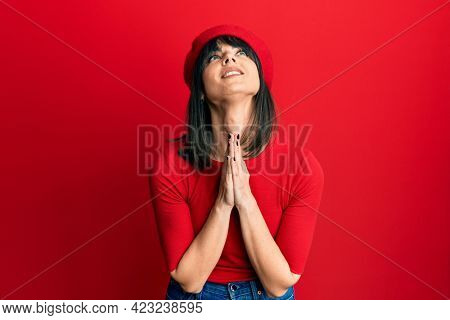Young hispanic woman wearing french look with beret begging and praying with hands together with hope expression on face very emotional and worried. begging.