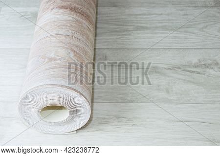 Rolled Up Roll Of Beige Linoleum With Wood Texture On White Wood Floor. Home Renovation And Improvem