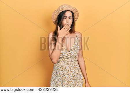 Young hispanic girl wearing summer hat bored yawning tired covering mouth with hand. restless and sleepiness.