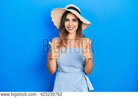 Young hispanic girl wearing summer hat success sign doing positive gesture with hand, thumbs up smiling and happy. cheerful expression and winner gesture.