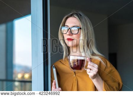 Business woman, teacher with laptop standing on terrace. Girl drinking coffee on fresh air, work, study from home. Long distance communication. Staying connected