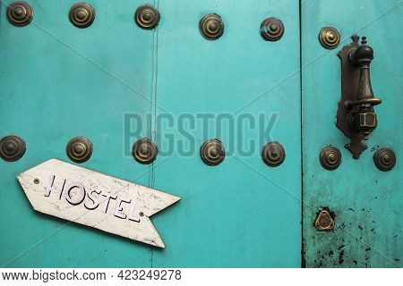 Old Rusty Blue Door With Hostel Arrow Sign Pointing The Doorknocker. Cheap And Fun Youth Hostel Conc
