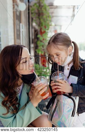 Stock Photo - Mom And Little Daughter With Takeaway Drinks In A Cafe. Opening A Cafe. Work Cafe With