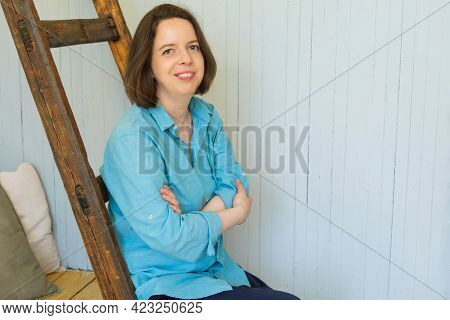 Young Brunette Woman With Shoulder-length Hair Lies On Pillow, Her Head Resting On Her Hands. Woman