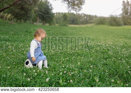 A Child Sits Alone On A Soccer Ball On A Park Lawn Because No One Wants To Play Soccer With The Girl