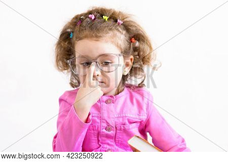Serious, Brooding, Cute Smart Little Girl In Funny Big Glasses Reading A Paper Books, Straightening
