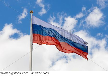 Russian Flag Flutters In The Wind, Lower Angle. The Flag Of The Russian Federation On A Pole Waving