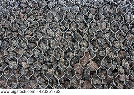 Part View Of Gabion Fence Filled With Granite Stones Supported By Chain Link Fence, Background
