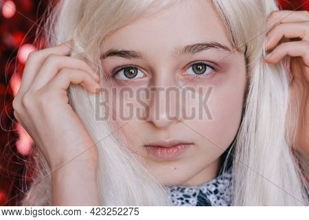 A Series Of Portraits Of Emotional Girls. Schoolgirl On A Red Background Portrait. Blonde.